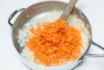 Shredded carrots added to the deep skillet with diced onions