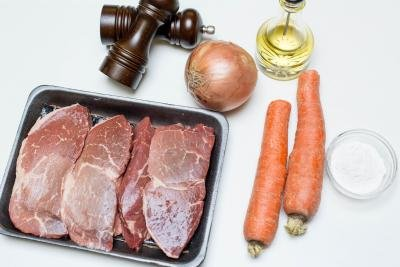 Ingredients on the table including; 2 carrots, beef, a bowl of flour, an onion, salt and pepper and oil