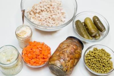 Ingredients on table include; carrots chopped into circles in a bowl, a jar of marinated mushrooms, a bowl of peas, bowl of pickles, jar of onions, jar of mayo, and bowl of chicken