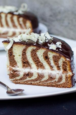 Zebra Cake slice on a plate with a spoon next to it