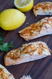 Baked Salmon on a cutting board with lemons besides the fillets