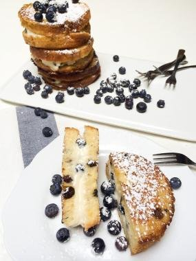 Stuffed French Toast stacked in a tower on one plate and on the plate next to it it is cut in half