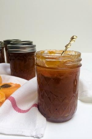 Apricot Jam in a jar opened with a spoon in the jar