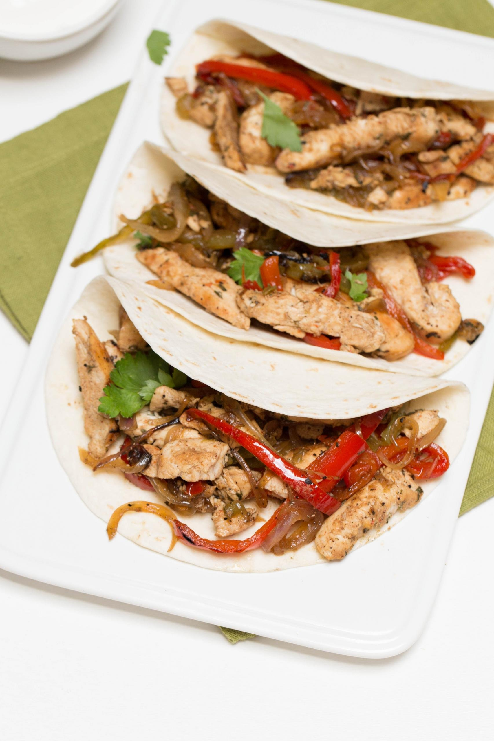 Chicken Fajitas tacos in a row on a plate