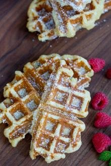 Belgian Waffles with powdered sugar on a cutting board with raspberries next to them