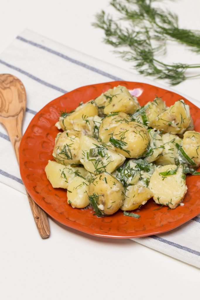 Creamy Herbed Potatoes on a plate with a wooden spoon besides it