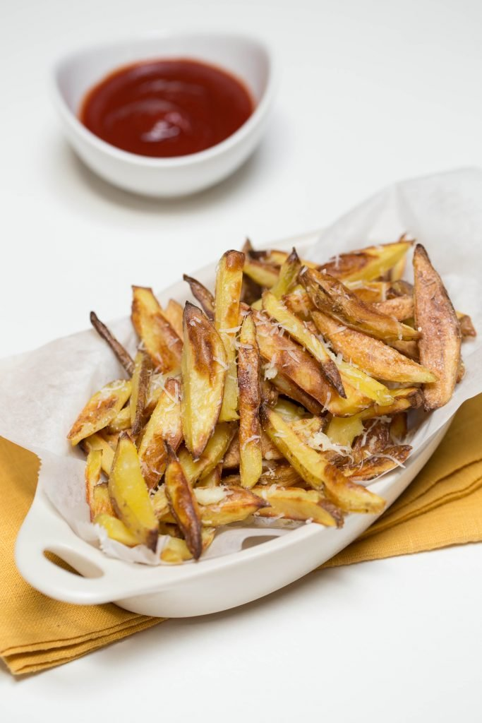 Crispy Baked Fries in a serving bowl with cheese sprinkled on top of the fries