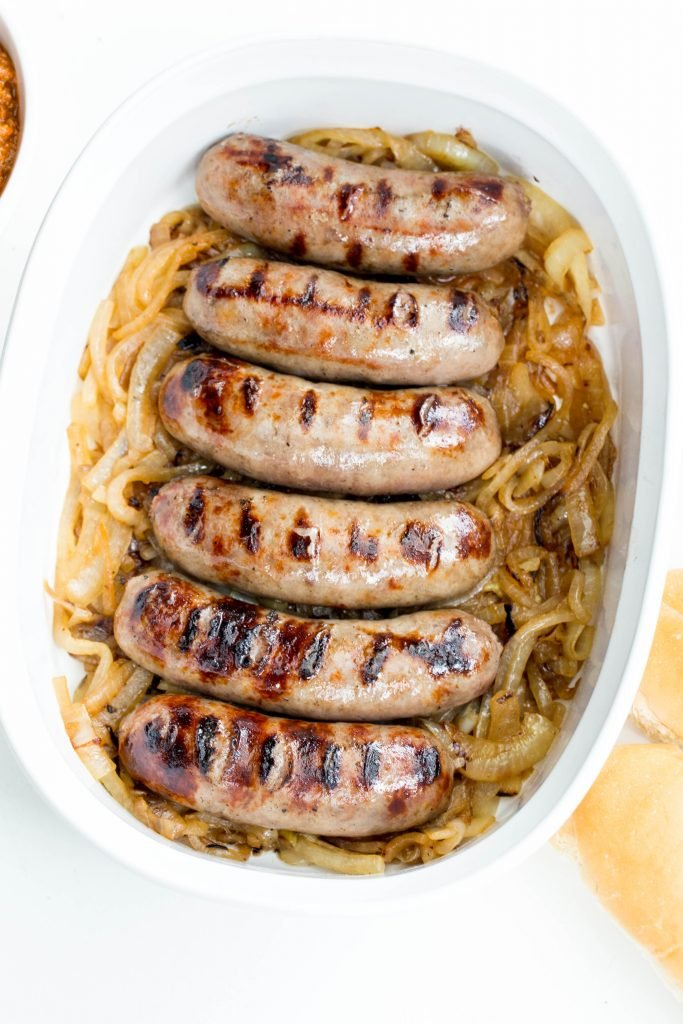 Johnsonville Beer Bratwurst on top of caramelized onions in a ceramic baking pan