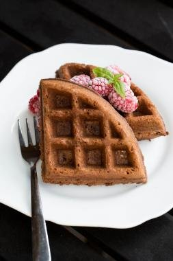 Chocolate Waffles on a plate with frozen raspberries on top of the waffles