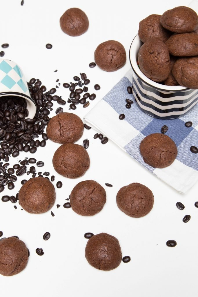 Chocolate Mocha Cookies on the table with coffee bean spread around the cookies and cookies in a jar