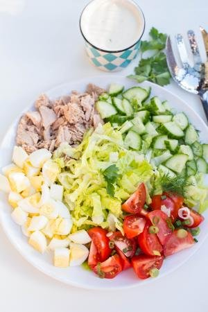 A serving dish of tuna Cobb Salad with dressing in a jar besides the plate with the salad