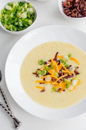 Creamy Potato Soup in a bowl with a little bowl of green onions and a bowl of bacon next to the soup