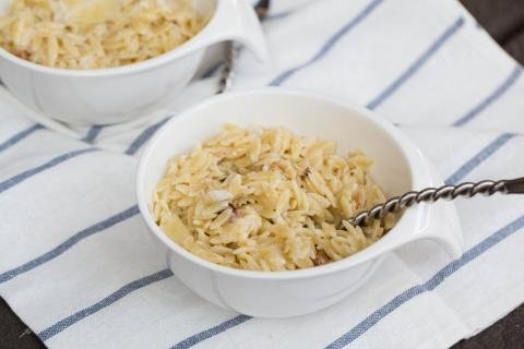 Creamy Orzo Bacon Pasta in a small bowl with a spoon in the pasta