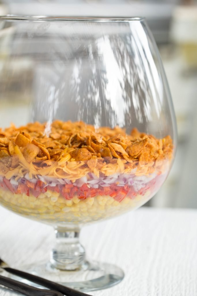 Fritos Chili Cheese Salad layered in a large glass bowl