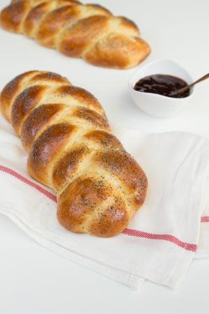 European Easter Bread on a kitchen towel with jam in a bowl besides it