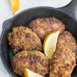Buckwheat Meat Patties in a small iron skillet with lemon wedges