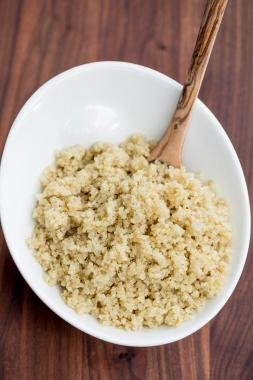 Quinoa in a bowl with a wooden spoon in it
