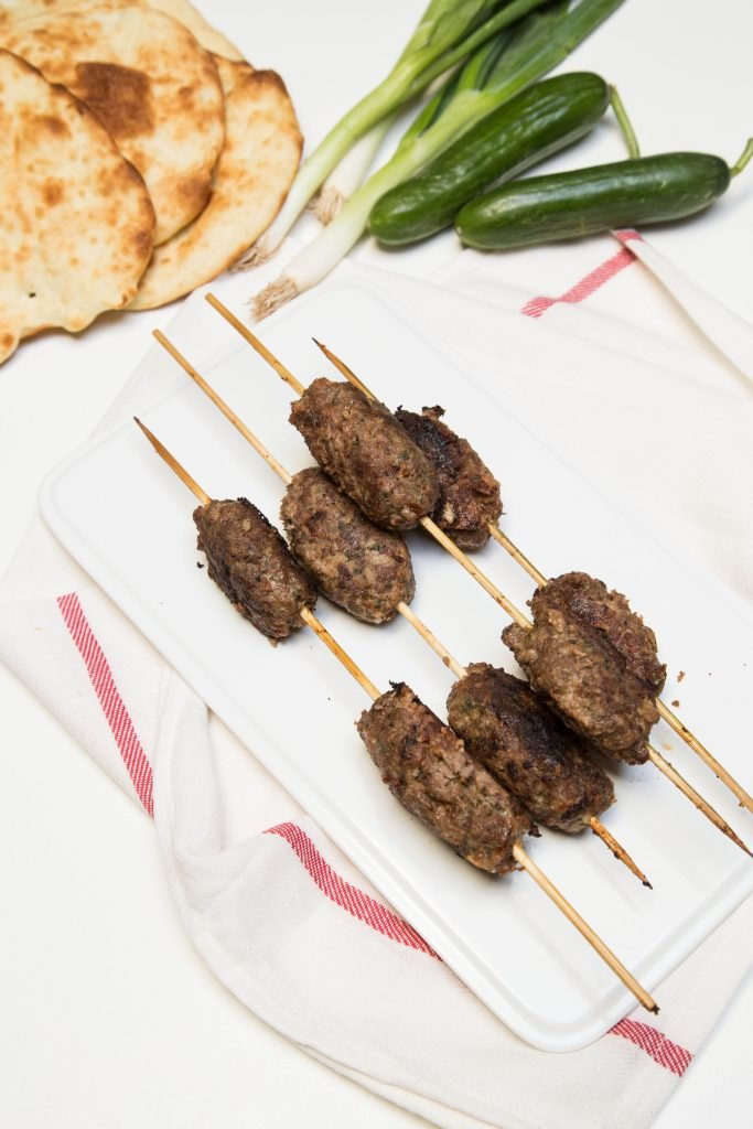 Beef Kofte Kebab on a plate with green onions, cucumbers and naan bread above the plate