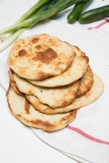 Naan Bread on a kitchen towel with green onions and onions besides it