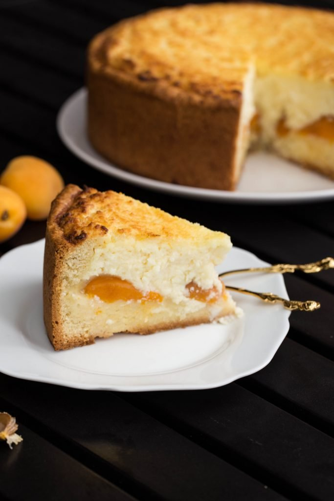 Apricot Farmer Cheese Cake slice on a plate with a spoon next to it
