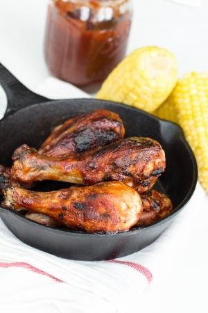 BBQ Chicken in an iron cast skillet with corn on the side