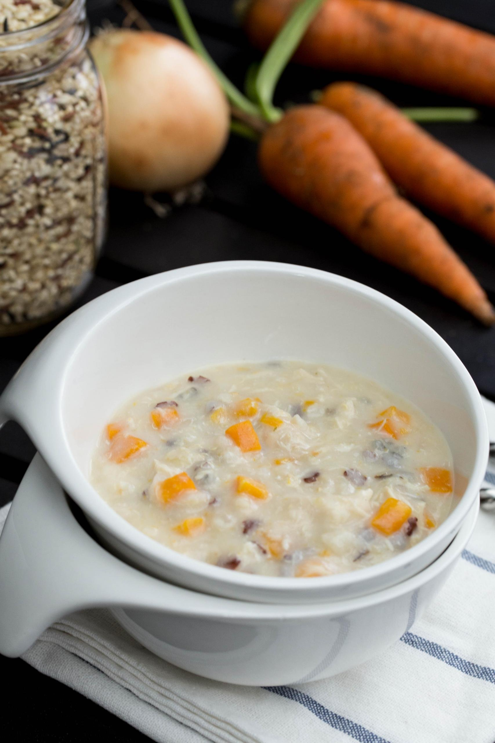 Chicken Wild Rice Soup in a bowl with jar with quinoa and rice blend behind it and 3 carrots