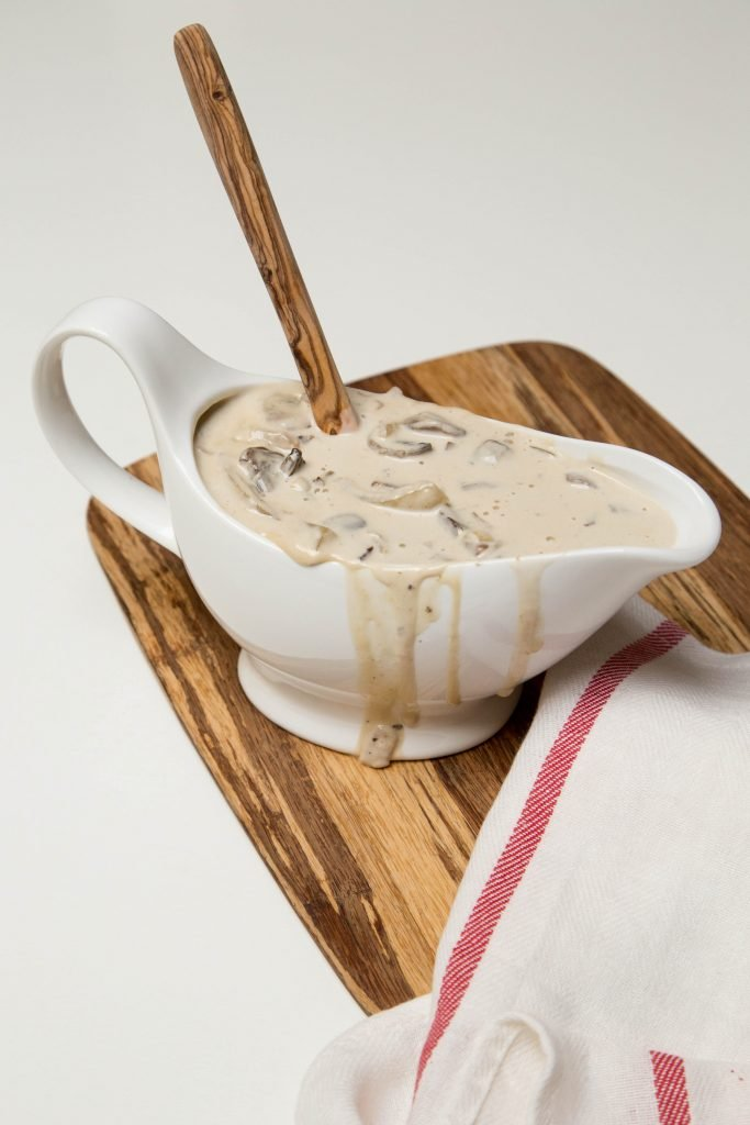 Creamy White Wine Mushrooms in gravy boat on cutting board with a spoon inside