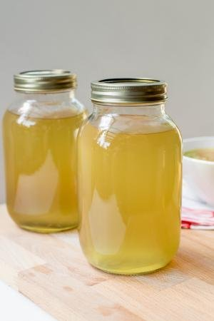 Homemade Chicken Broth in jars that are standing on a cutting board