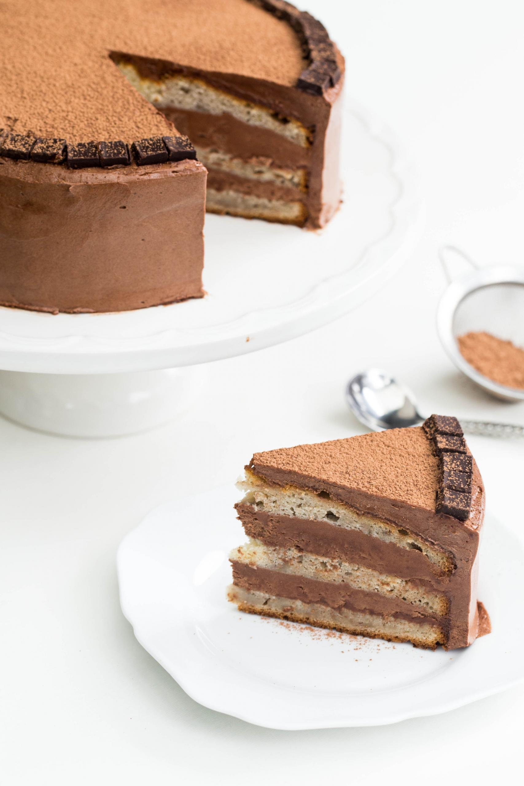 Chocolate Nutella Banana Cake slice on a plate with the full cake behind it