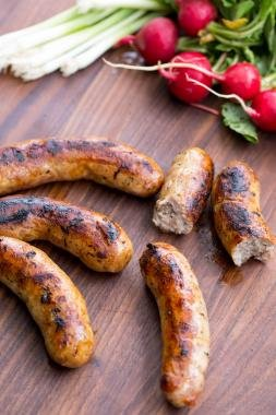 Homemade Sausage links on a cutting board with green onions and radishes