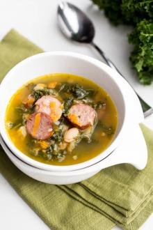 Sausage Kale Soup in a bowl standing on a kitchen towel