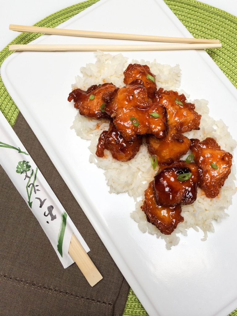 Sweet and Sour Chicken on rice on a plate with chopsticks besides the plate