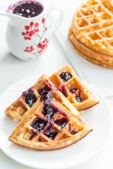 Buttermilk Waffles cut into 4 on a plate with jam spread on top of them