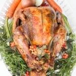 Roast Turkey on a serving tray with garnish all around it