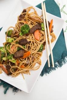 Beef Lo Mein on a plate with chopsticks on the plate