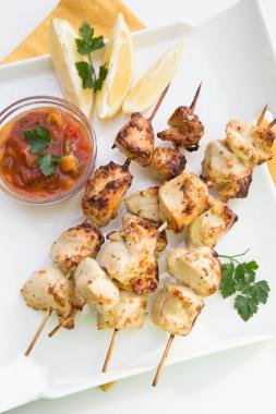 Chicken Kebabs on a plate with lemon slices next to it and salsa in a small bowl next to the kebabs