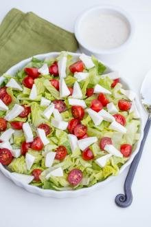 Tomato Mozzarella Lettuce Salad in a serving tray with a little bowl of dressing besides it