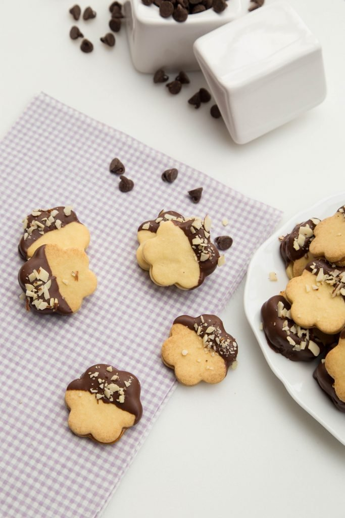 Dulce De Leche Sandwich Cookies on a table napkin with chocolate chips spread around the cookies