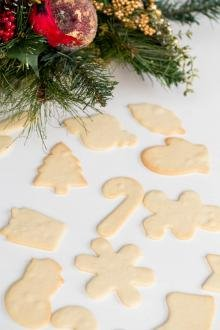 THE Perfect Sugar Cookies spread on the table in the shape of candy canes, presents, snowmen, mittens, ornaments, and snowflakes