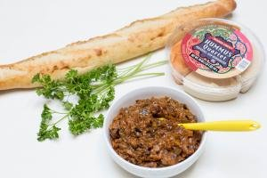Ingredients on the table including; parsley, baguette, hummus and eggplant ikra spread in a bowl