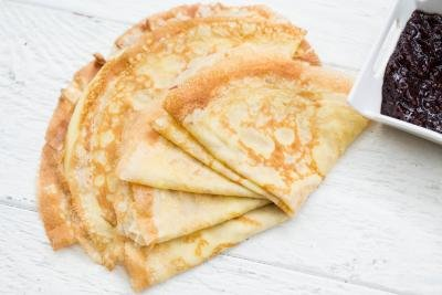 Perfect Crepes on a table with a bowl of jam besides it