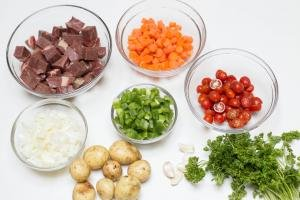 5 bowls one with diced beef, one with diced onions, one with diced carrots, one with green bell peppers, one with halved abby tomatoes, parsley, garlic cloves and potatoes