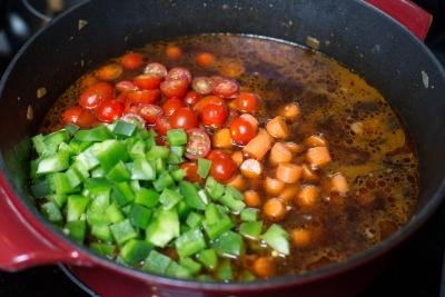 Green peppers, tomatoes and carrots added into a pot with beef, onions and water