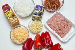 Ingredients on the table including; 4 red bell peppers, a bowl of cheese, a bowl of corn, ground turkey, a can of black beans, salsa in a bowl, rice in a bowl, and taco seasoning