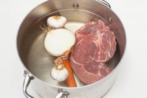 A pot filled with water and beef, a carrot, garlic and half an onion in the pot