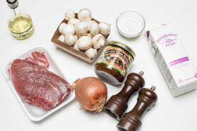 Ingredients on the table including; an onions, salt and pepper, better than bouillon beef, beef, heavy whipping cream, mushrooms, flour in a bowl and oil