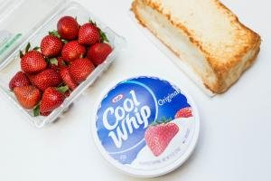 Ingredients on the table; strawberries, cool whip and angel bread