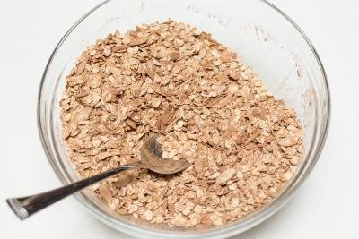 Oatmeal, sliced almonds and cocoa powder mixed in a bowl