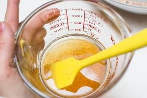 Vanilla extract, honey, and coconut oil combined in a measuring cup with a spatula