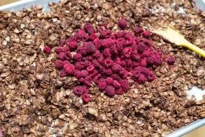 Chocolate Raspberry Granola on a baking pan with freezer dry raspberries added